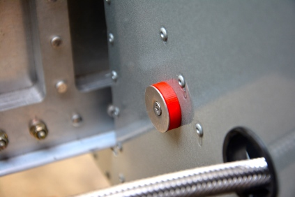 The red plastic isolator is shown with the aluminum plate and the screw mounted on the fuselage side.